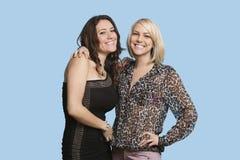 Porträt von zwei schönen multi ethnischen Frauen, die über blauem Hintergrund lächeln Lizenzfreie Stockbilder