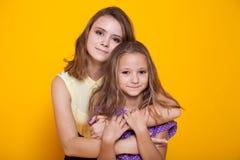 Porträt von zwei Schwestern auf einem gelben Hintergrund 1 Lizenzfreie Stockfotos