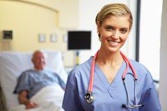 Porträt weiblichen Krankenschwester-With Patient In-Hintergrundes Lizenzfreie Stockfotografie
