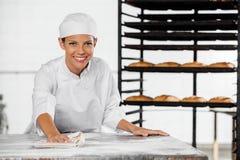 Porträt weiblicher Bäcker-Cleaning Flour From-Tabelle Stockbild