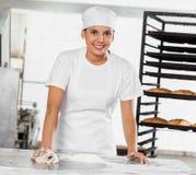 Porträt weiblicher Bäcker-Cleaning Flour From-Tabelle Stockfotos
