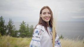 Porträt, welches das überzeugte sorglose kaukasische Mädchen trägt das lange Sommermodekleid genießt bezaubert, Kamera betrachten stock video