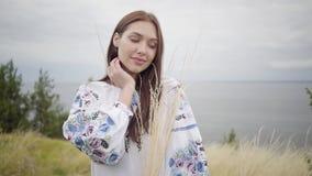 Porträt, welches das überzeugte sorglose kaukasische Mädchen trägt das lange Sommermodekleid genießt bezaubert, Kamera betrachten stock video footage