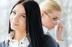Porträt zwei schönen junge Frauen Brunette u. blonde Mitarbeiter nähern sich Bürofenster tagsüber Lizenzfreie Stockfotos