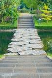 Porträtansicht von Zementschritten, unten führend in Richtung zu einer Kanalsteinbrücke und jenseits in einen reizenden Gartenpar lizenzfreie stockfotos