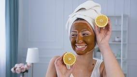 Porträtaufnahme der attraktiven Frau aufwerfend mit Hälfte zwei der Zitrone auf Augen mit Maske auf dem Gesicht stock video