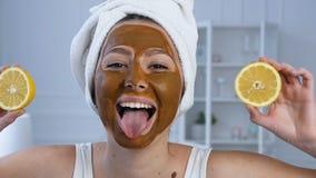 Porträtaufnahme der attraktiven Frau mit Hälfte zwei der Zitrone auf Augen mit Maske auf dem Gesicht stock video footage