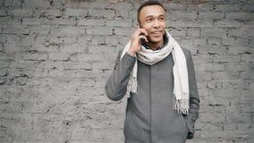 Porträtaufnahme des afroen-amerikanisch Mannes sprechend am Telefon Hübscher Afroamerikanerkerl in einem Mantel und in einem Scha stock video