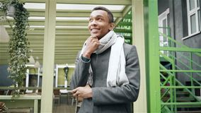 Porträtaufnahme des hübschen nachdenklichen Afroamerikanermannes, der einen Mantel und einen Schal trägt Handzeitlupeporträt stock video footage