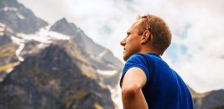 Porträtbergsteigermann schaut auf den Bergspitzen Stockfotos
