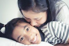Porträtbildliebes-Familienmutter auf der Kusstochter Nettes M?dchenl?cheln sch?n und gl?cklich auf Bett stockfoto