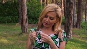 Porträtblondine, die auf weißer Kamille im Sommerwald schätzen stock video footage