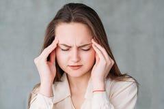 Porträtdruckkopfschmerzen-Notentempel der jungen Frau stockfoto
