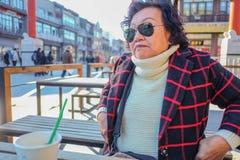 Porträtfoto von den asiatischen älteren Frauen, die Coffe auf Qianmen-Straße die berühmte Straße in Peking trinken stockbild