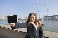 Porträtfrau, die Selbstporträt durch Handy gegen London-Auge in London, England, Großbritannien nimmt Lizenzfreie Stockfotos