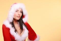 Porträtfrau, die Weihnachtsmann-Kostüm auf Gelb trägt Stockfoto