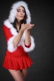 Porträtfrau, die Weihnachtsmann-Kostüm auf Schwarzem trägt Stockfotos