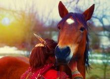 Porträtfrau und -pferd in im Freien Die Frau, die ein Pferd umarmt und hat Feder in ihrem Haar In sul Licht lizenzfreies stockbild