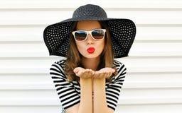 Porträtfrau, welche die roten Lippen senden süßen Luftkuß im schwarzen Sommerstrohhut auf weißer Wand durchbrennt stockfotos