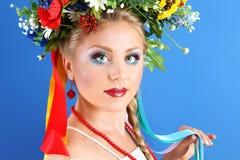 Porträtfrauenmake-up mit Blumen auf blauem Hintergrund stockfotografie