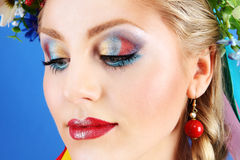 Porträtfrauenmake-up mit Blumen auf blauem Hintergrund stockbilder
