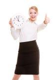 Porträtgeschäftsfrau, die sich Uhr und Daumen zeigt Zeit Lizenzfreie Stockfotos