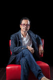 Porträtgesicht des alten asiatischen Mannes der Jahre 45s, der herein auf rotem Sofa sitzt Lizenzfreies Stockbild