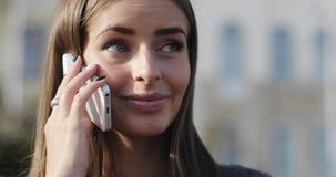 Porträtgesicht des jungen schönen Mädchens mit Klammern auf ihren Zähnen sprechend am Handy stock video