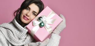 Porträtgriffgeschenk der jungen Frau Lächelndes glückliches Mädchen auf rosa Hintergrund stockbild