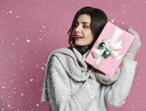 Porträtgriffgeschenk der jungen Frau Lächelndes glückliches Mädchen auf rosa Hintergrund lizenzfreie stockfotos