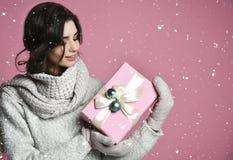 Porträtgriffgeschenk der jungen Frau Lächelndes glückliches Mädchen auf rosa Hintergrund stockbilder