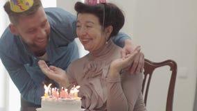 Porträtgroßmutter, die am Tisch vor dem kleinen Kuchen mit vielen Kerzen sitzt Erwachsener Enkel, der die Frau umarmt stock footage