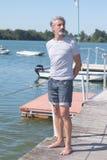 Porträtgutaussehender mann auf dem Pier, der ruhig weg schaut Stockfotos