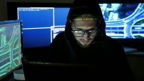 Porträthacker, männlicher Hacker, der an Computer arbeitet, während grüne Codezeichen über Gesicht im dunklen Büro nachdenken, ge stock video