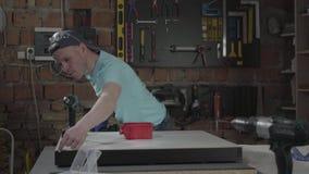 Porträthandwerkeringenieur gerichtet auf die Bohrung eines Lochs mit Werkzeug auf dem Hintergrund einer kleinen Werkstatt mit Ins stock footage