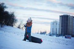 Porträtjunge mit Schläuche im Schnee, Winterzeit, Glückkonzept Stockfoto