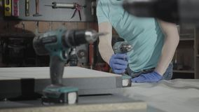 Porträtjunger Vorlageningenieur gerichtet auf die Bohrung eines Lochs mit Werkzeug auf dem Hintergrund einer kleinen Werkstatt mi stock video footage