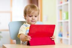 Porträtkind, das zuhause Laptop, Auflagencomputer verwendet stockfotografie