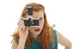 Porträtmädchen mit Fotokamera und dem roten Haar Lizenzfreie Stockfotos