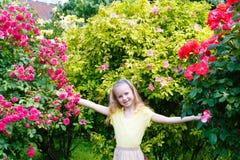Porträtmädchen und Rosenbusch Stockfoto