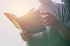 Porträtmann tragendes T-Shirt Mannaufenthalt in der Bibliothek für das Ablesen Lizenzfreie Stockfotos