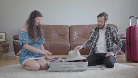 Portr?tmann und -frau, die zu Hause auf dem Boden vor einem ledernen Sofa, einen Koffer vor Reise verpackend sitzt E stock video footage