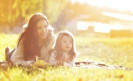 Porträtmutter und -kind auf dem Gras im Herbst stockfoto