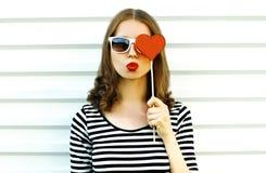 Porträtnahaufnahmefrau, welche die roten Lippen senden den süßen Luftkuß versteckt ihr Auge mit geformtem Lutscher des roten Herz lizenzfreies stockfoto