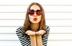Porträtnahaufnahmefrau, welche die roten Lippen senden süßen Luftkuß auf weißer Wand durchbrennt stockfoto