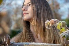 Porträtprofil einer jungen Frau im Winter im Garten auf Roheisenzaun mit Frost Hoarfrost stockbild