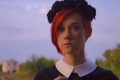 Porträtrothaarigemädchen mit schwarzen Kronenblumen Lizenzfreies Stockfoto