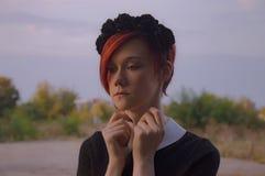 Porträtrothaarigemädchen mit schwarzen Kronenblumen Lizenzfreie Stockbilder