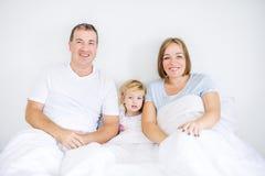 Porträts der glücklichen und liebevollen Familie im Sleepwear, der morgens Zeit der Kamera betrachtet Nette Eltern, die Spaß mit  Lizenzfreies Stockbild