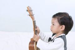 Porträts ein kleiner netter asiatischer Junge, der ein Interesse am Musical hat Stockfotos
